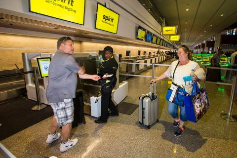 Brian Kile, left, and Amy Conn-Kile, right, both of Chicago, walk up to the Spirit Airlines aut ...