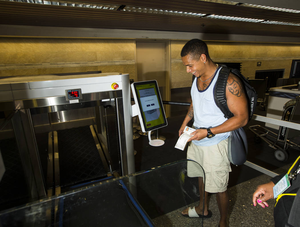 Jerrel Oneal, of Beaverton, Ore., uses the Spirit Airlines automated self-service bag drop syst ...