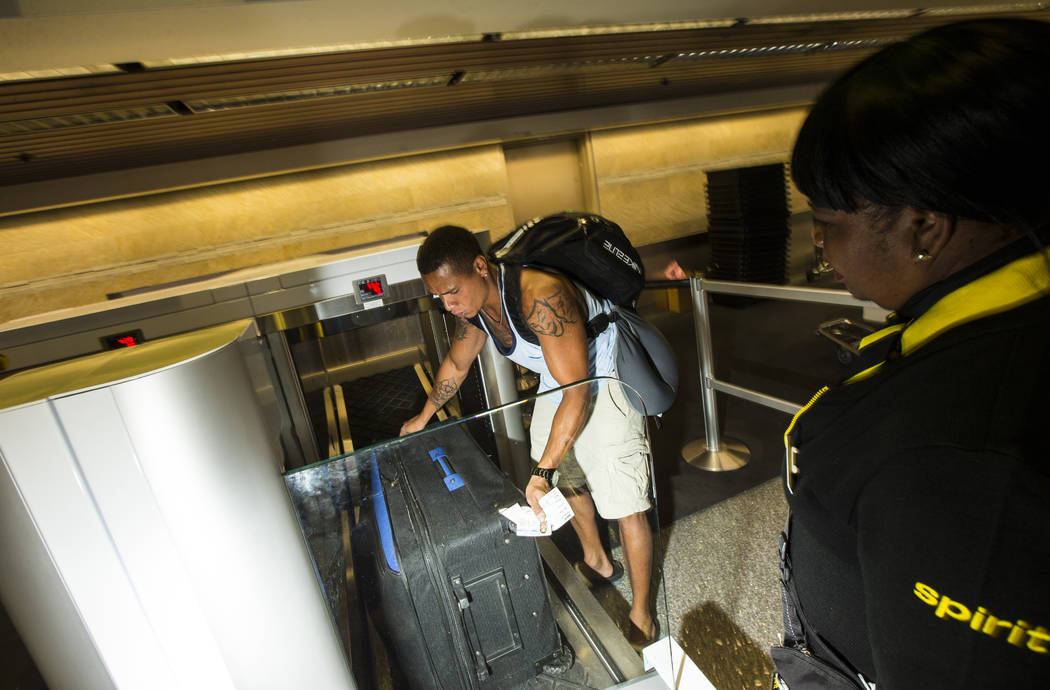 Jerrel Oneal of Beaverton, Oregon, use the Spirit Airlines automated self-service bag drop syst ...