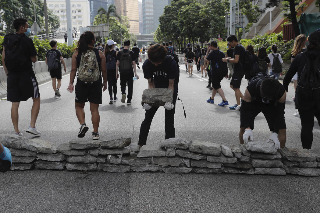 Protesters use stones to block a road in Hong Kong on Friday, June 21, 2019. Several hundred ma ...