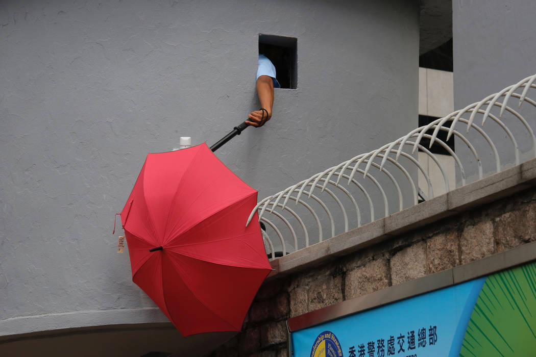 A police officer tries to remove an umbrella blocking the view of security cameras outside the ...