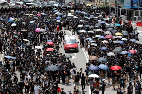 A taxi makes its way through a crowd of protesters gathered on a street near government offices ...