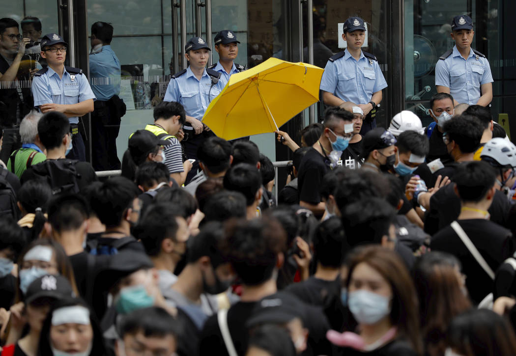 A protester holds out a yellow umbrella towards a line of police officers in Hong Kong Friday, ...