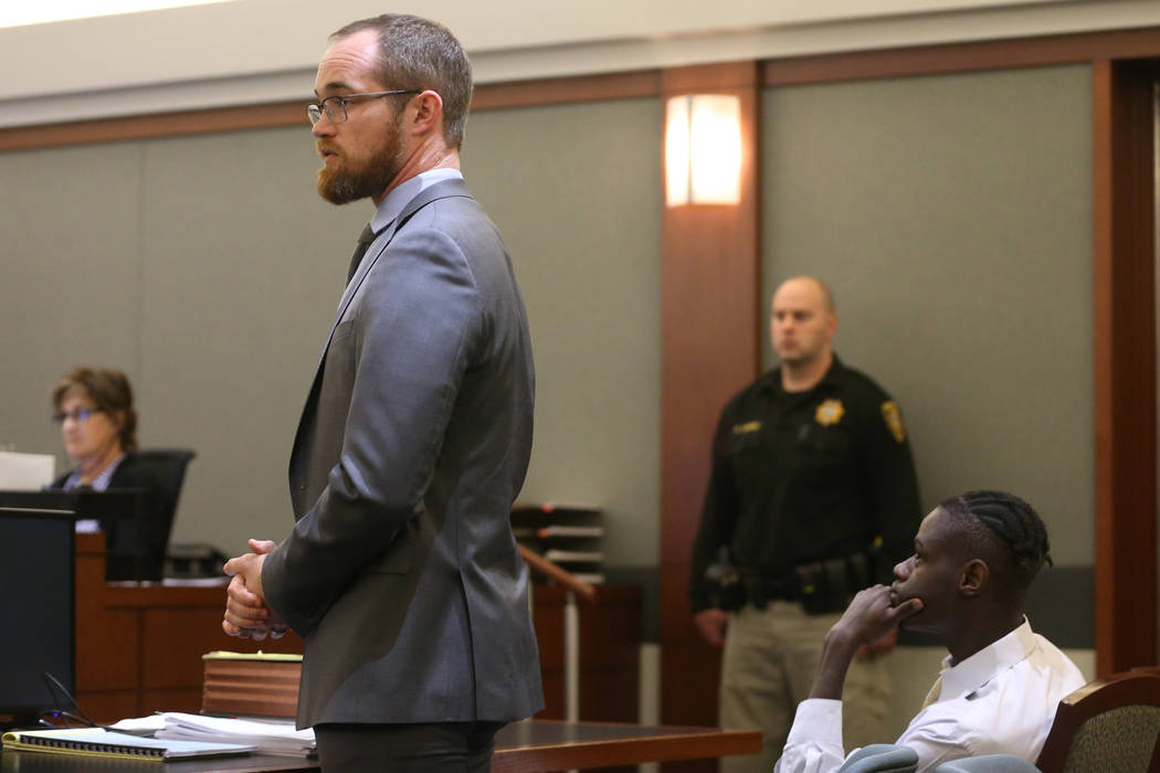Defense lawyer Chris Peterson, left, speaks at the Regional Justice Center in Las Vegas on Frid ...