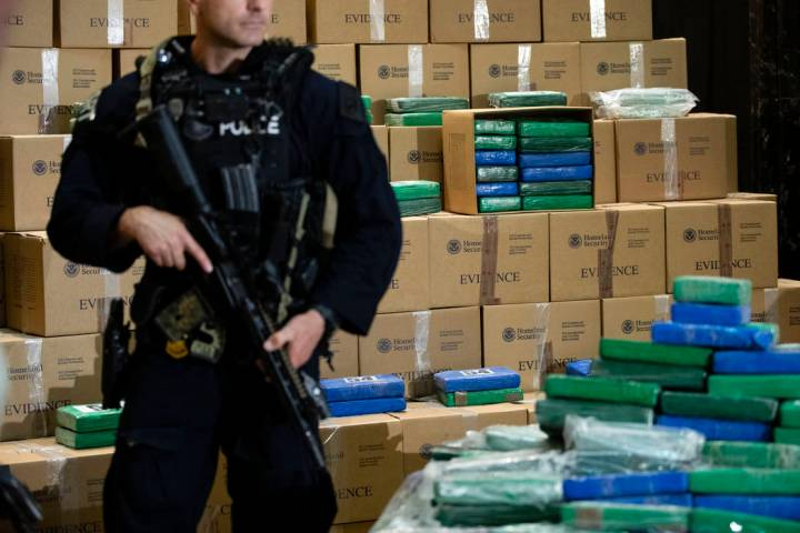 An officer stand guard over a fraction of the cocaine seized from a ship at a Philadelphia port ...