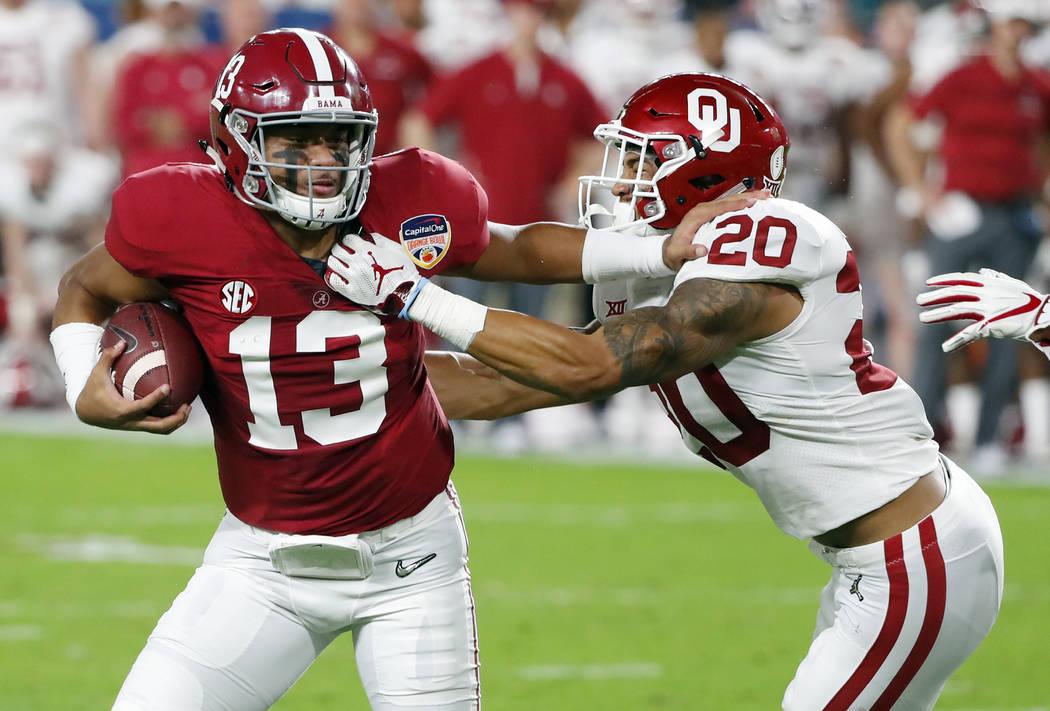 Alabama quarterback Tua Tagovailoa (13) fights off Oklahoma safety Robert Barnes (20), during t ...