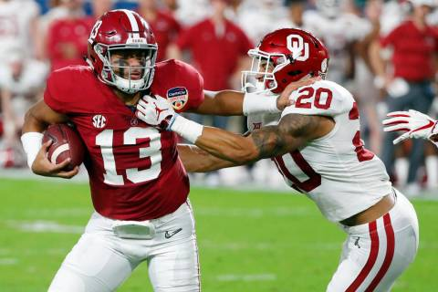 Alabama quarterback Tua Tagovailoa (13) fights off Oklahoma safety Robert Barnes (20), during t ...