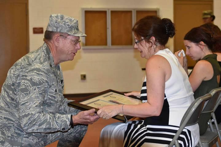 Nevada Adjutant General Brig. Gen. Bill Burks, left, presents Margie Gallagher her husband's po ...