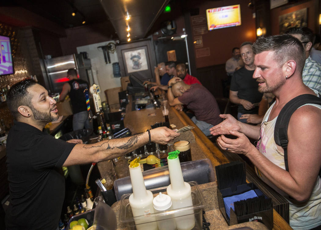 Bartender Eric Garcia, left, serves drinks to guests at Bastille on 3rd, the longest running LG ...