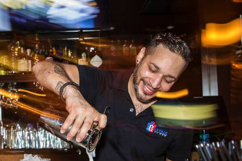 Bartender Eric Garcia makes drinks at Bastille on 3rd, the longest running LGBTQ bar in Las Veg ...
