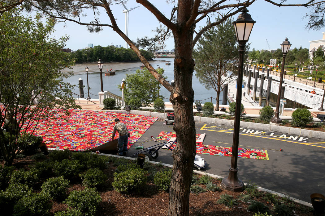 Workers cut carpet in front of the Mystic River as seen from the porte-cochere at Encore Boston ...