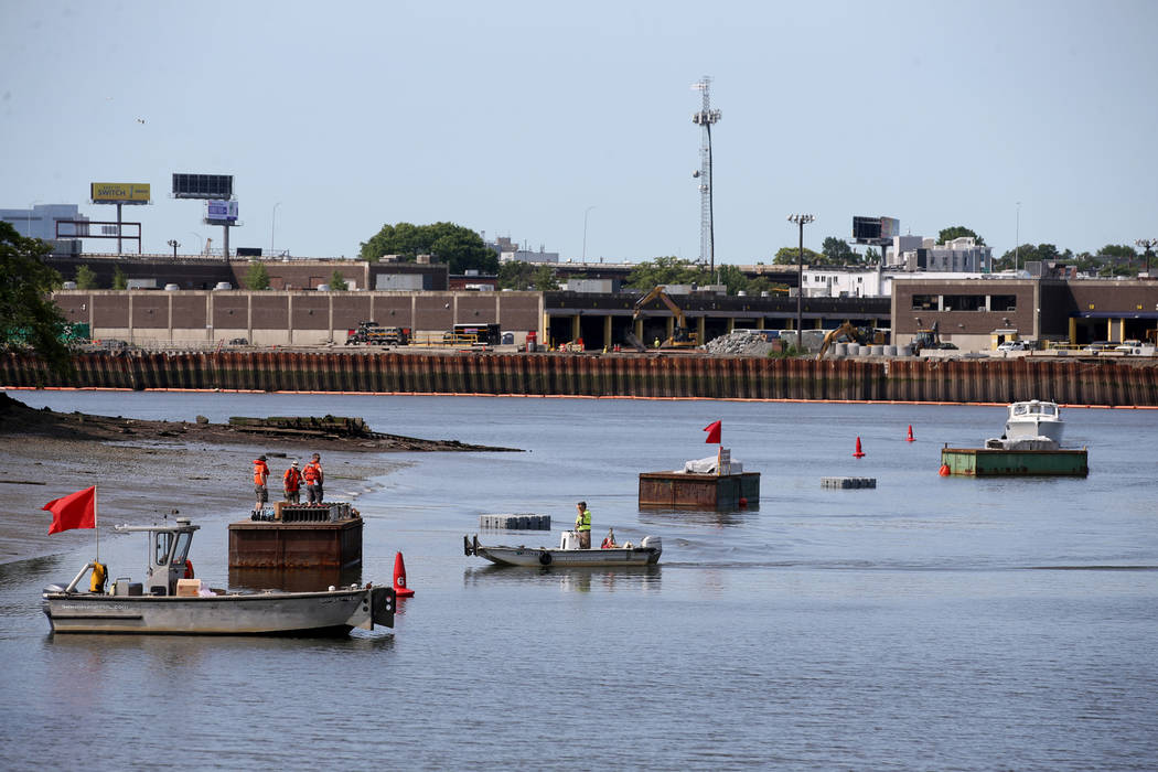 Workers prepare fireworks on barges on the Mystic River at Encore Boston Harbor in Everett, Mas ...