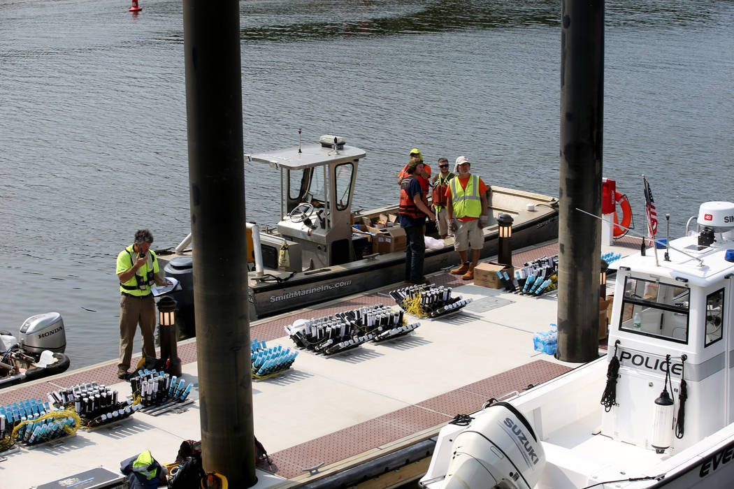 Workers prepare to move fireworks to barges on the Mystic River at Encore Boston Harbor in Ever ...