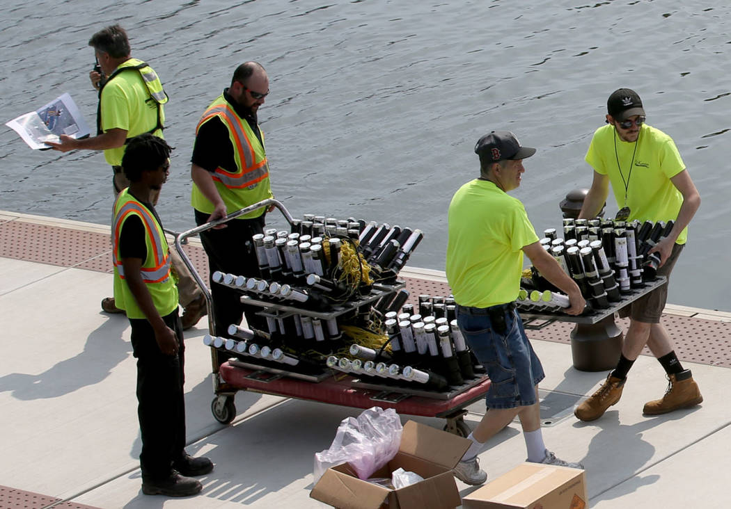 Workers move fireworks to barges on the Mystic River at Encore Boston Harbor in Everett, Mass., ...