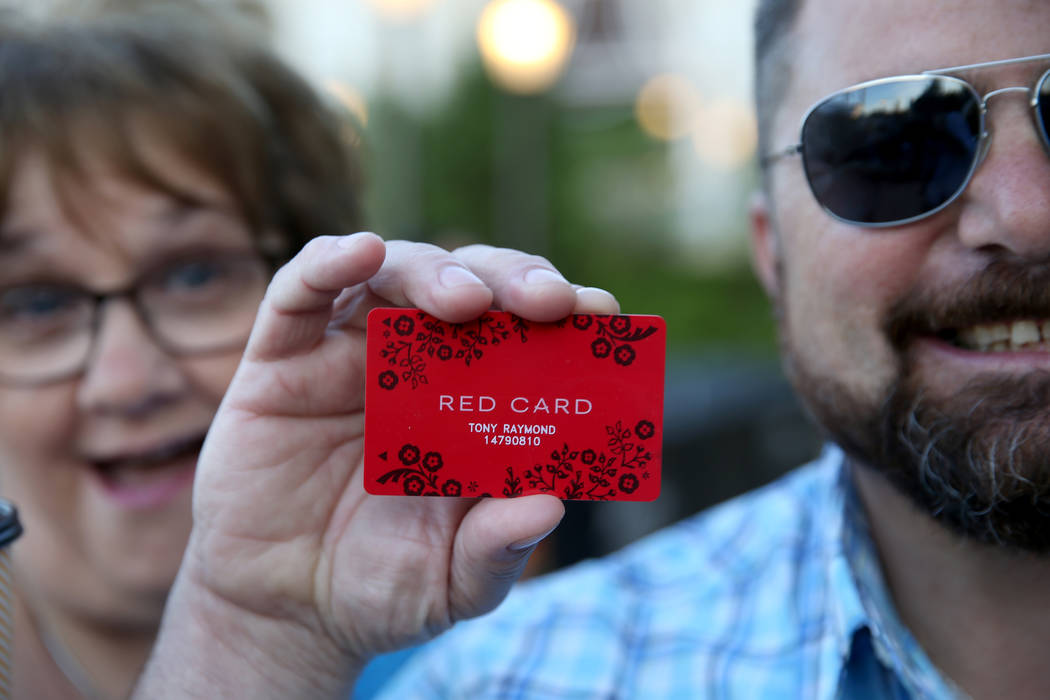 Tony Raymond, of Everett, Mass., shows his newly-acquired Red Card with Debbie Capozzi, of Wilm ...
