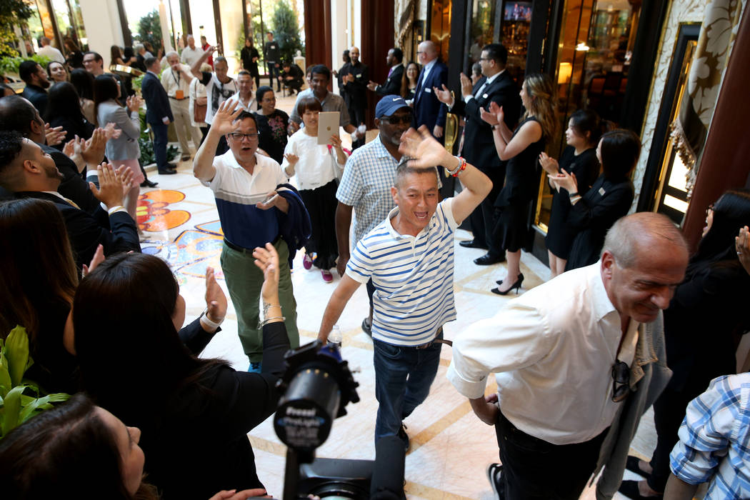 Employees cheer as some of the first guests arrive in the Garden Lobby during the opening of th ...