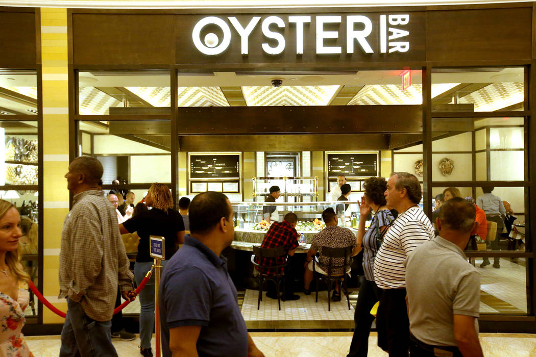 Guests walk past the Oyster Bar on opening day of the $2.6 billion Encore Boston Harbor in Ever ...