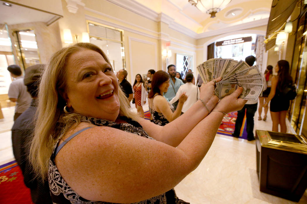 Tammy Akusis, of Abington, Mass., shows her winnings on opening day of the $2.6 billion Encore ...