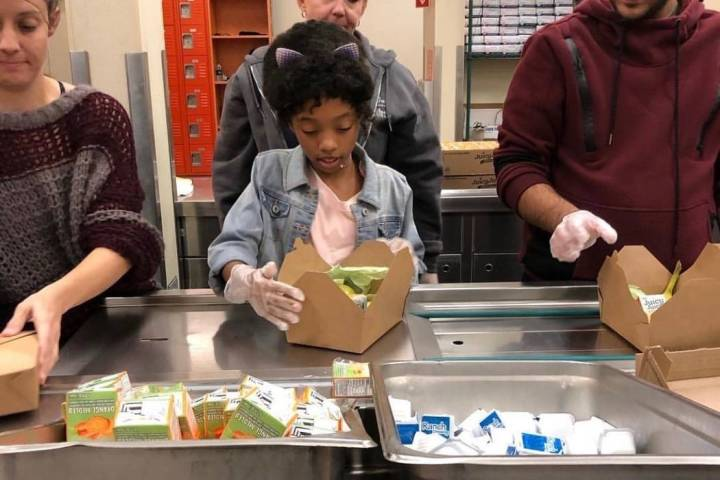 Jordyn Lenae, 11, helps pack lunches at Three Square. Jordyn said she believes every child shou ...