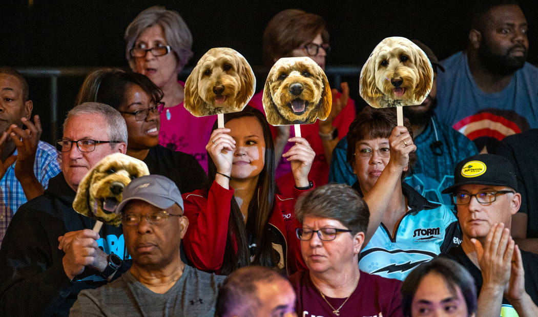 Fans hold up dog face placards when Shannon O'Keefe bowls a great frame in her semifinals match ...
