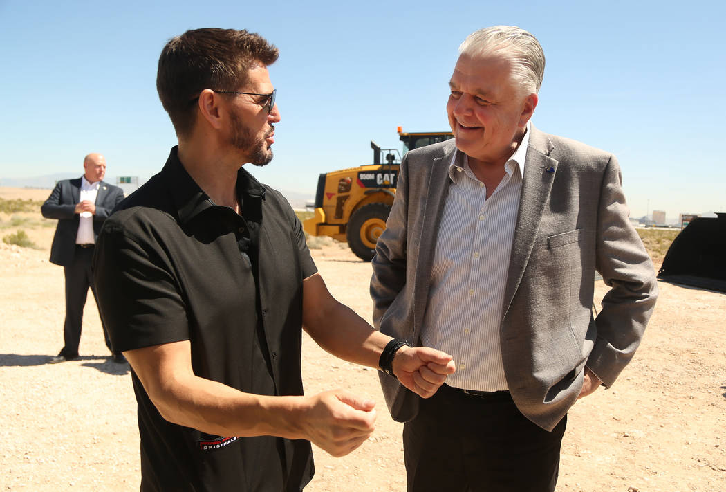 CEO of Switch Rob Roy, left, talks with Nevada Governor Steve Sisolak, right, during the ground ...