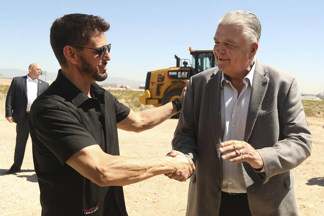 CEO of Switch Rob Roy, left, shakes hands with Nevada Governor Steve Sisolak, right, during the ...