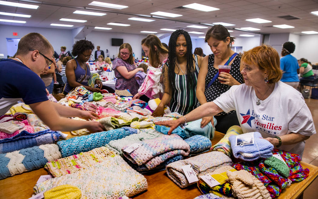 Roseann Voigt, with the Twisted Needle Knockers, right, points out all the free blankets and ot ...