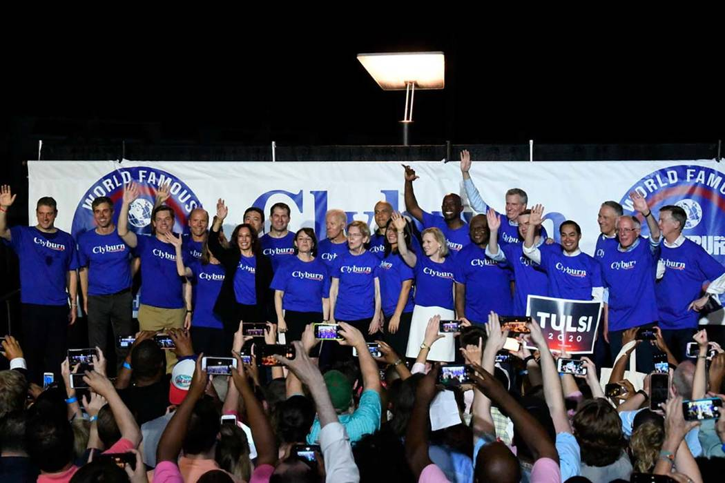 Twenty-one of the Democrats seeking the party's presidential nomination pose together after Hou ...