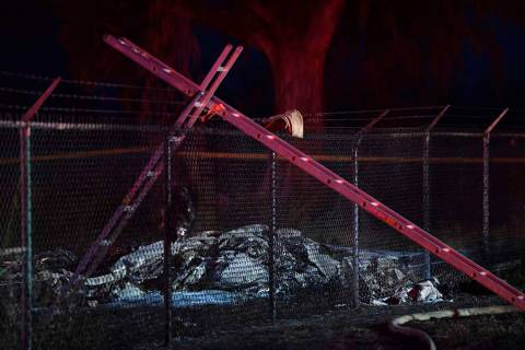 Remnants of an aircraft carrying nine people lies on the ground near a fence that surrounds Dil ...
