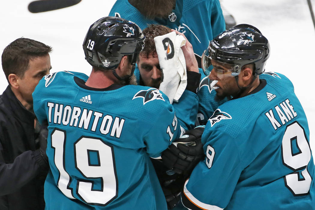 Sharks center Joe Pavelski, middle, is helped off the ice by Sharks left wing Evander Kane (9) ...