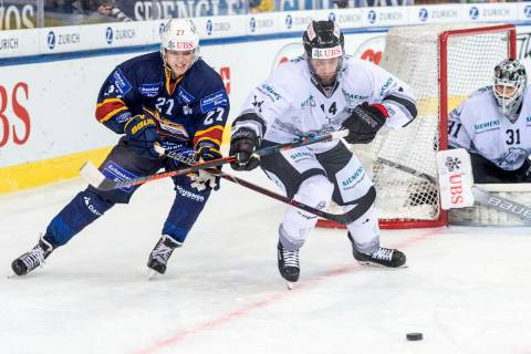 Magnitogorsk's Pavel Dorofeyev, left, against Ice Tigers's Marcus Weber challenge for the puck ...