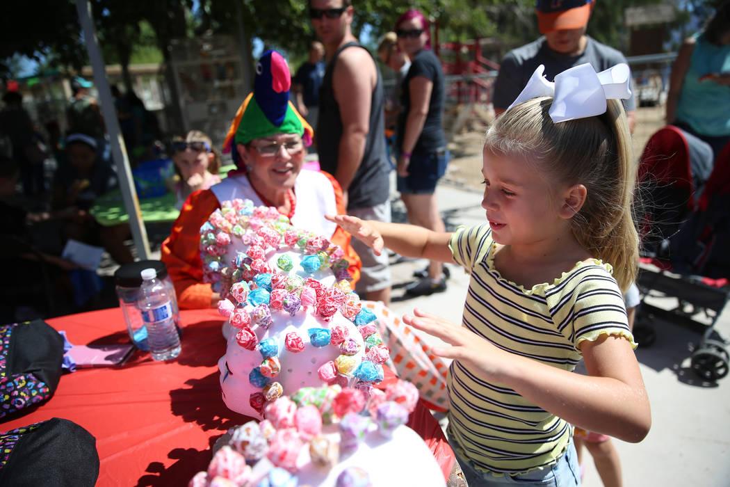 Gianna Bertuccini, 7, picks a lollipop as volunteer Carol Bell looks on during the Founder's Da ...
