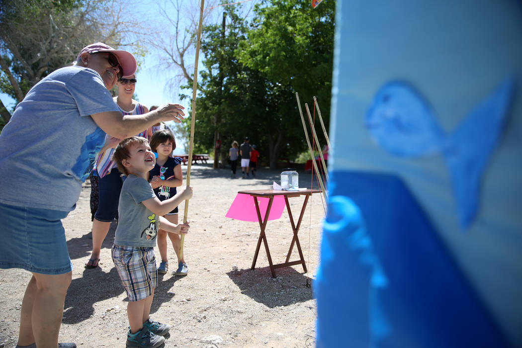 Volunteer Marcella Booth, left, helps Jackson Sharpe, 3, with a fishing game, as his mother Dan ...