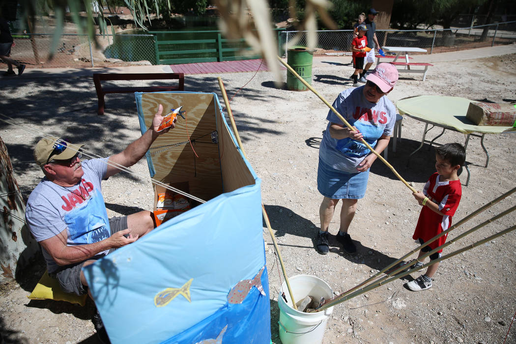 Volunteers Richard Booth, from left, and his wife Marcella, assist Evan Albidrez, 5, of Las Veg ...