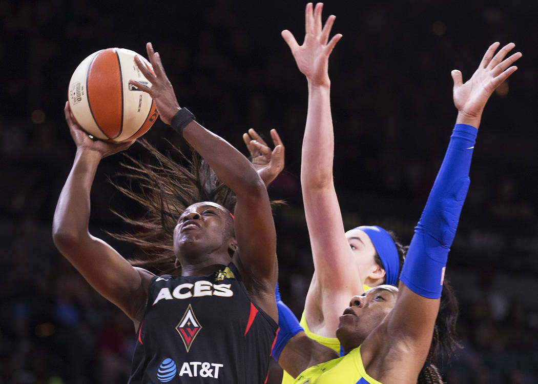 Las Vegas Aces guard Jackie Young (0) drives past Dallas Wings guard Allisha Gray (15) and Dall ...