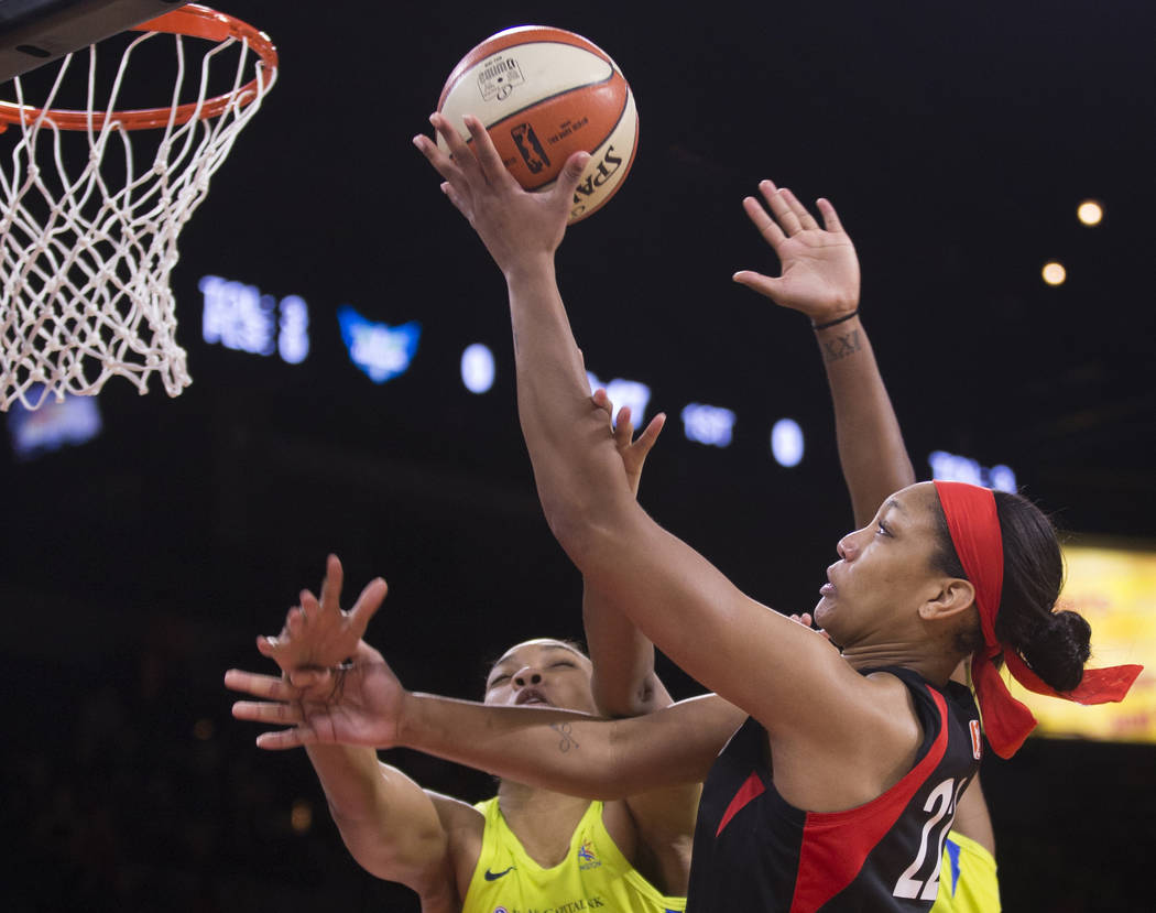 Las Vegas Aces center A'ja Wilson (22) slices to the rim past Dallas Wings center Imani McGee-S ...