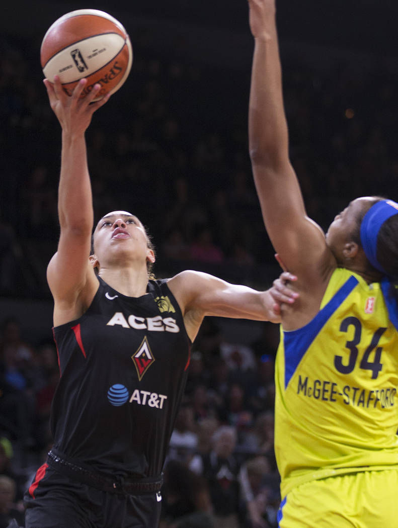Las Vegas Aces forward Dearica Hamby (5) slices to the rim past Dallas Wings center Imani McGee ...