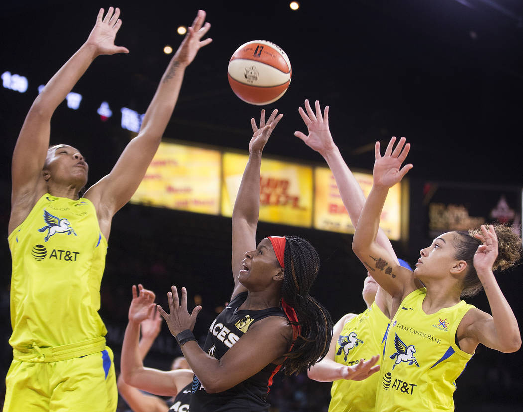 Las Vegas Aces guard Sugar Rodgers (14) splits Dallas Wings center Imani McGee-Stafford (34) an ...