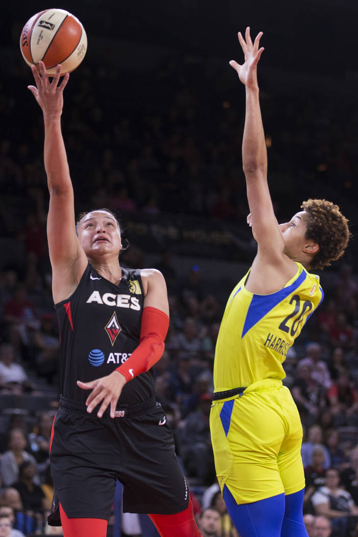 Las Vegas Aces guard Kayla McBride (21) drives past Dallas Wings forward Isabelle Harrison (20) ...