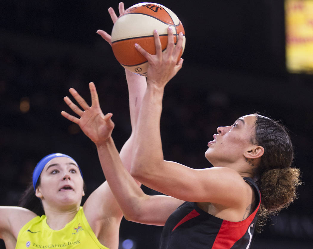 Las Vegas Aces forward Dearica Hamby (5) drives past Dallas Wings forward Megan Gustafson (13) ...