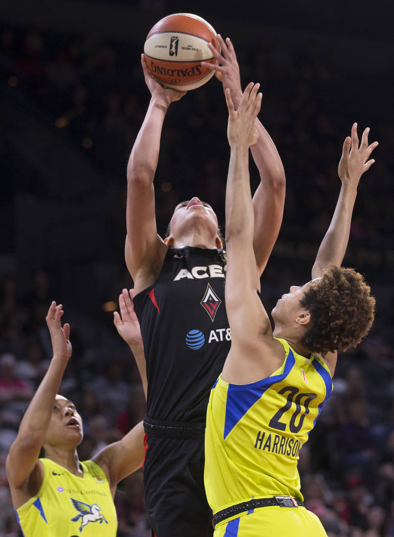 Las Vegas Aces forward Dearica Hamby (5) grabs a rebound over Dallas Wings forward Isabelle Har ...