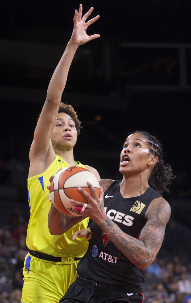 Las Vegas Aces forward Tamera Young (1) drives past Dallas Wings forward Isabelle Harrison (20) ...