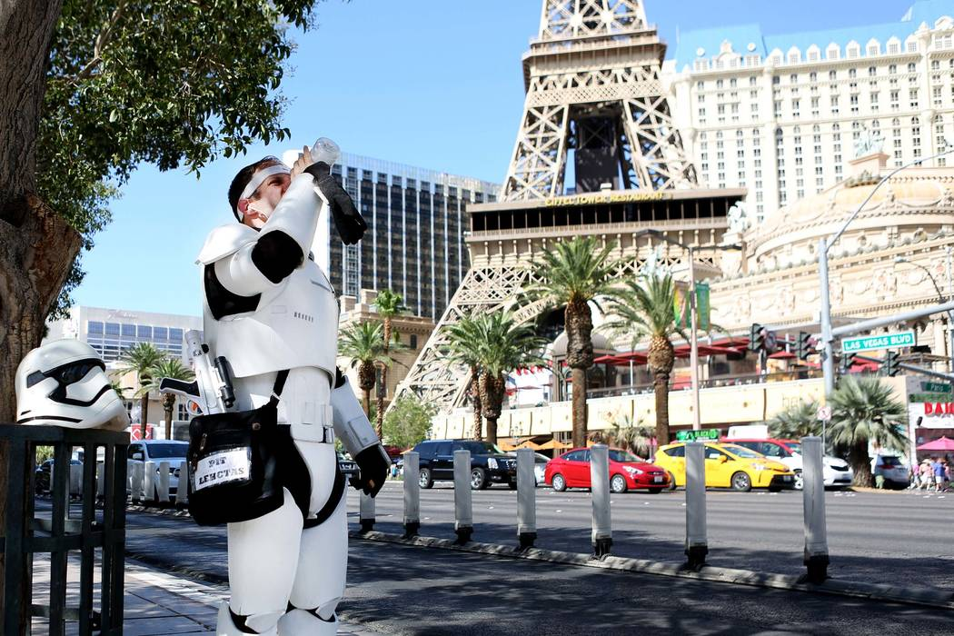 Street performer Adam Reynolds stays hydrated as he works in the hot weather near the Bellagio ...
