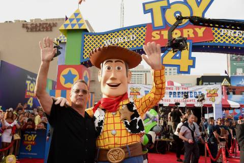 "Tom Hanks, left, poses with his character Woody as he arrives at the world premiere of ""To ..."