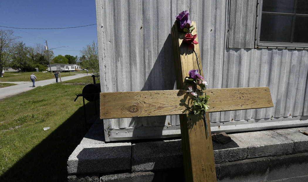 In this photo taken Wednesday, April 17, 2019, a cross leans against an abandoned house trailer ...