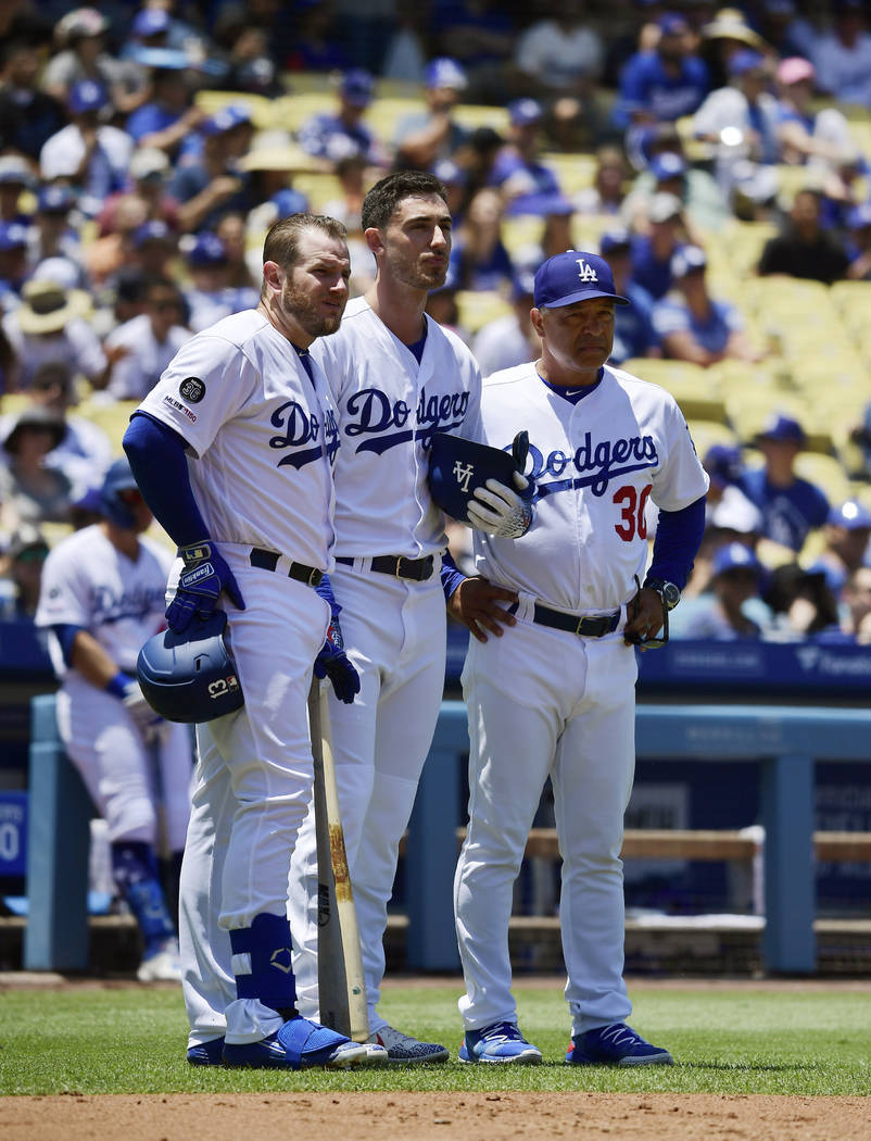 Los Angeles Dodgers Max Muncy, left, stand with Cody Bellinger, center, and manager Dave Robert ...