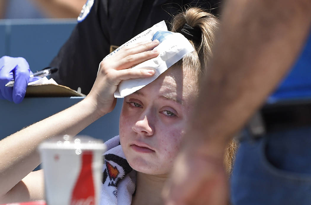 A young fan holds ice to her head after being hit with a foul ball hit by Los Angeles Dodgers' ...