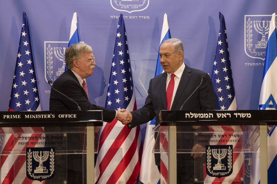 Israeli Prime Minister Benjamin Netanyahu, right, shakes hands with U.S. National Security Advi ...