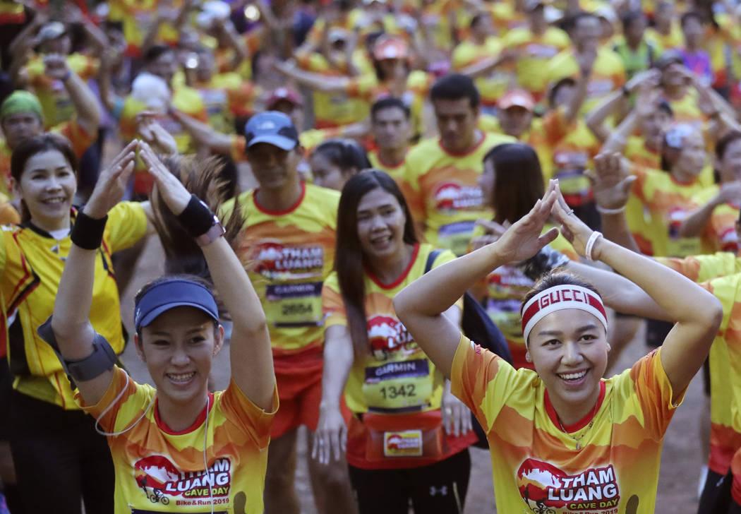 Runners warn up before the start of a marathon and biking event in Mae Sai, Chiang Rai province ...