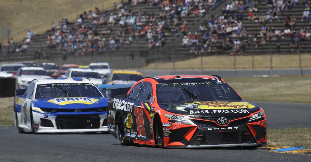 Martin Truex Jr., right, leads through a turn during a NASCAR Sprint Cup Series auto race Sunda ...